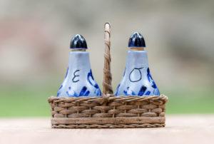 Ein Essigfläschchen und Ölfläschchen mit Korb für den Tisch